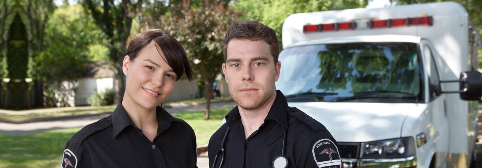 Two paramedics standing in front of ambulance vehicle